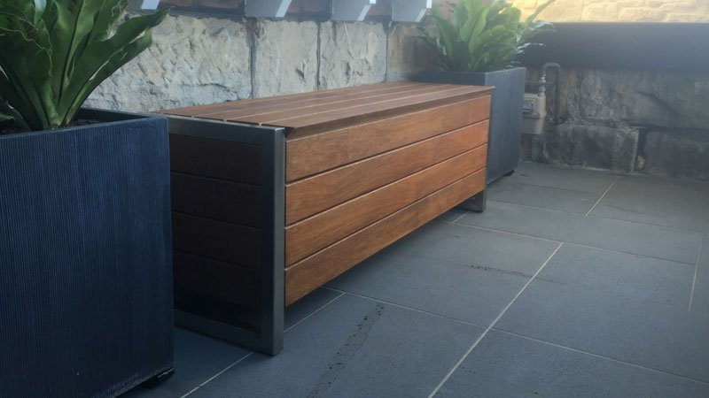 Commissioned water tight hardwood storage bench with stainless legs.