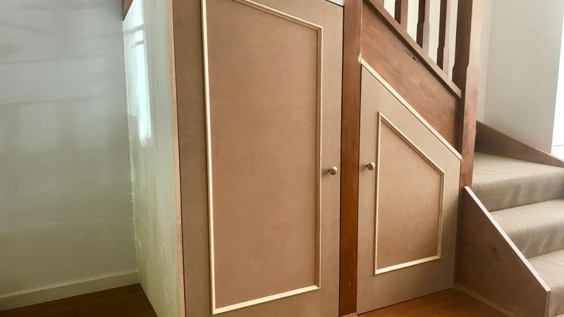 Custom built-in under-stair storage unit.